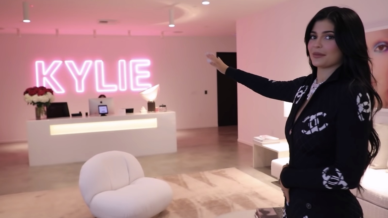 Kylie Jenner pointing to her cosmetic brand logo -KYLIE