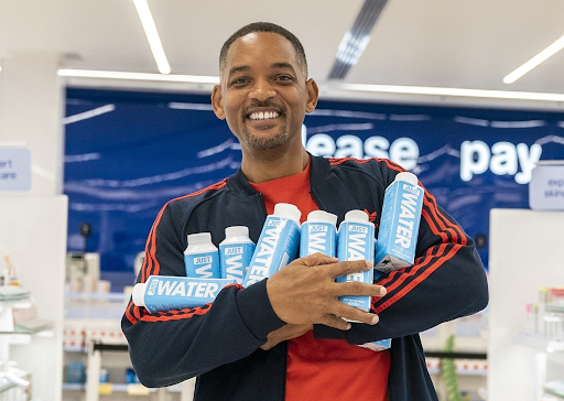 Will smith standing with his brand of water - Just water